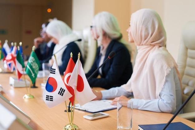 Bos vlaggen van verschillende andere landen op tafel met rij interculturele sprekers die deelnemen aan de conferentie Premium Foto