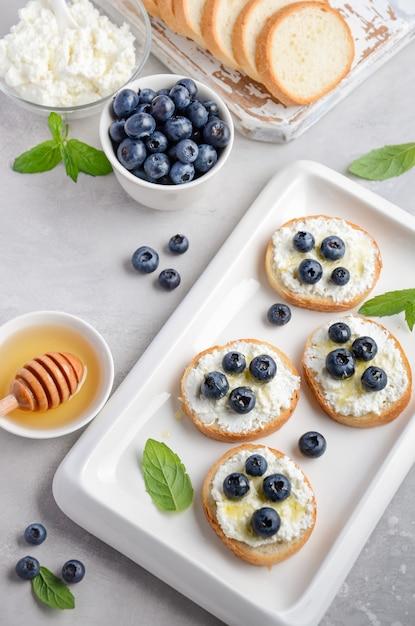 Bosbessen en honingsandwiches, gezond ontbijtconcept. Premium Foto