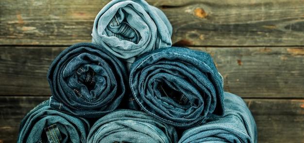 Bosje spijkerbroeken gedraaid op een houten muur, modieuze kleding Gratis Foto