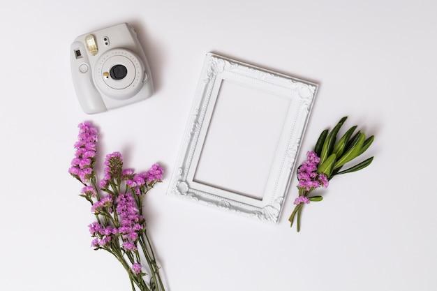 Bossen van bloemen dichtbij fotolijst en camera Gratis Foto