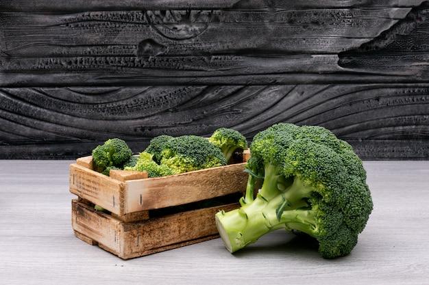 Bossen van broccoli in houten doos dichtbij de gehele verse broccoli Gratis Foto