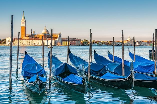 Boten geparkeerd in het water in venetië en de kerk van san giorgio maggiore op de achtergrond Gratis Foto