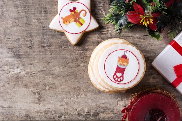 Boterkoekjes van kerstmis die met kerstmisgrafiek worden verfraaid, op houten lijst copyspace Premium Foto