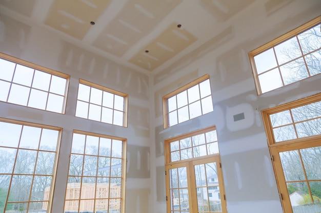 Bouw bouwsector nieuwe woningbouw interieur gipsplaat tape en afwerking details geïnstalleerde deur voor een nieuw huis vóór installatie Premium Foto