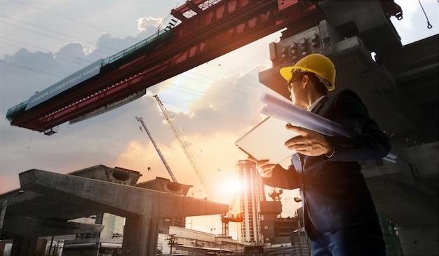 Bouw ingenieur manager toezicht op de voortgang van bts station en tablet met blauwdruk in handen. Premium Foto