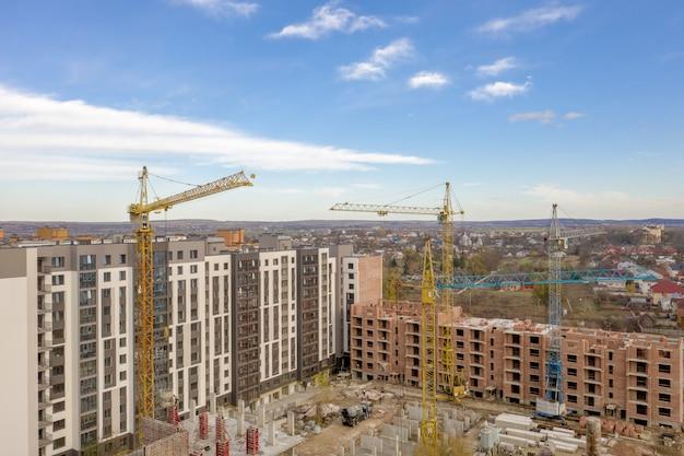 Bouw van een nieuw wooncomplex met meerdere verdiepingen. kranen en bouwplaats. moderne flatgebouwen worden gebouwd Premium Foto