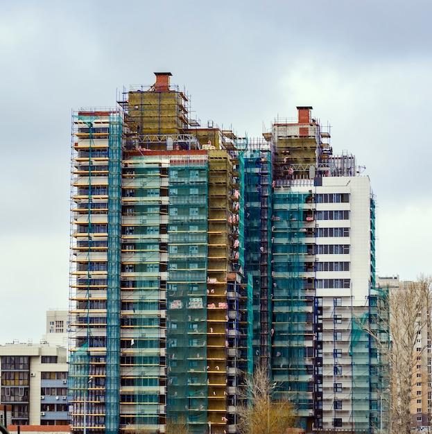 Bouw van woningbouw met meerdere verdiepingen. bouwwerkzaamheden aan de isolatie van de gebouwbekleding. Premium Foto
