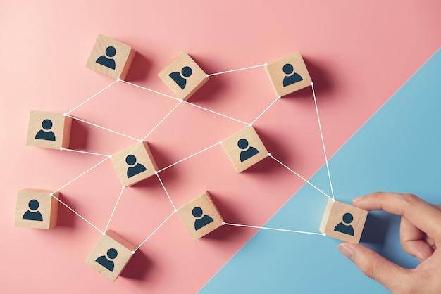Bouwend een sterk team, houten blokken met mensenpictogram op blauwe en roze achtergrond, personeel en beheersconcept. Premium Foto