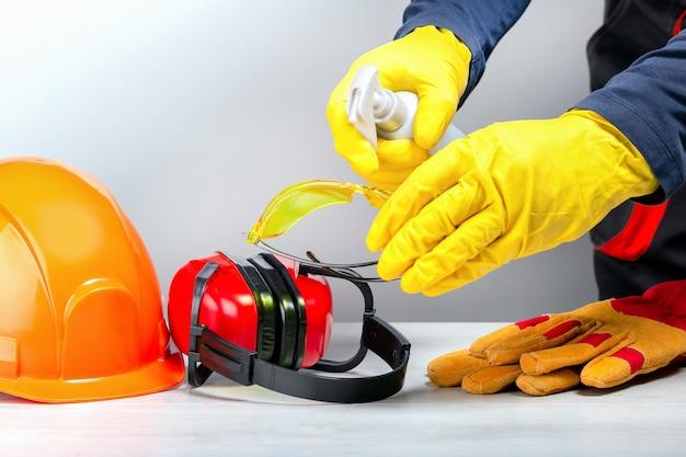 Bouwer die beschermende kleding op de werkplek desinfecteert. Premium Foto