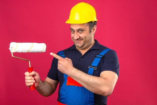 Bouwersmens die eenvormige bouw dragen en veiligheidshelm die zich met verfrol bevinden die en vinger glimlachen om verfrol over geïsoleerde roze muur te schilderen Gratis Foto