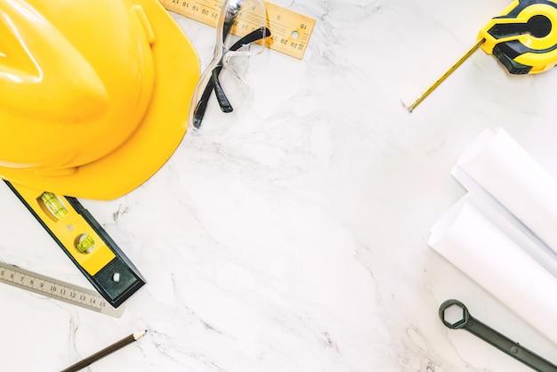 Bouwhulpmiddelen met helmveiligheid op witte marmeren achtergrond Premium Foto