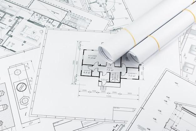Bouwkundige constructietekeningen in een rol gedraaid, bouwprojecten op papier. Premium Foto