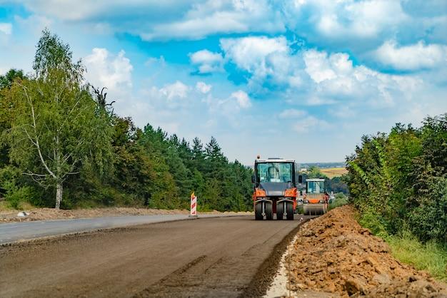 Bouwmachines voor wegenwerken passeren nieuw asfalt in de zomer van bomen Premium Foto
