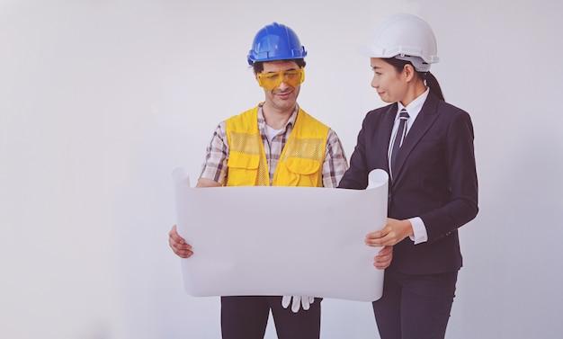 Bouwmanager en ingenieur die blauwdrukken bekijken Premium Foto