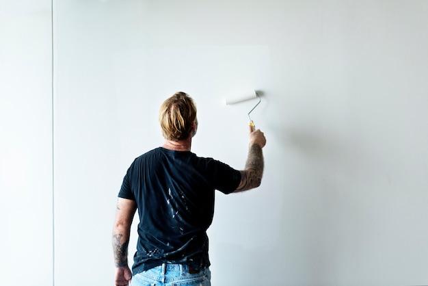 Bouwvakker die de muur schildert Gratis Foto