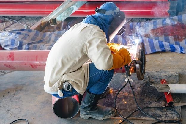 Bouwvakker die rode staalpijp voor brandalarmsysteem in nieuwe bouw lassen Premium Foto