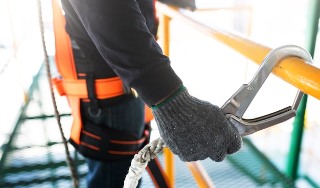 Bouwvakker die veiligheidsuitrusting en veiligheidslijn draagt die bij de bouw werkt Premium Foto
