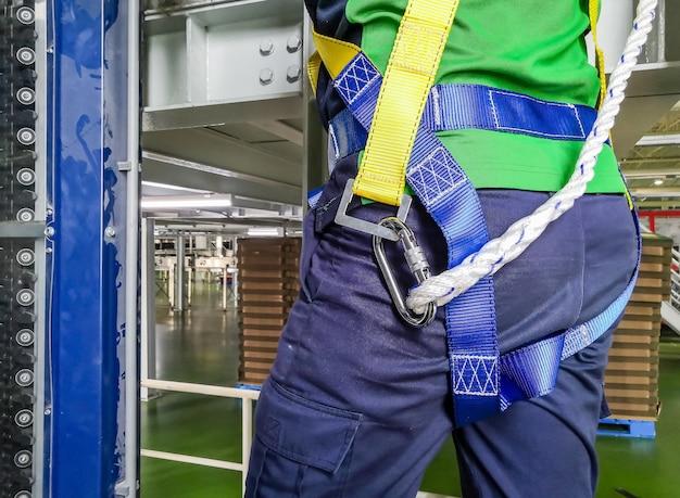 Bouwvakker gebruik veiligheidsharnas en veiligheidslijn werken aan een nieuwe bouwplaats Premium Foto