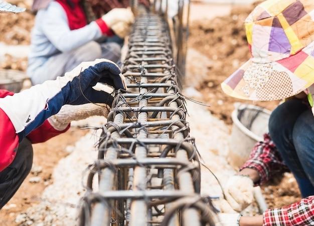 Bouwvakkers installeren stalen staven in balken van gewapend beton Gratis Foto