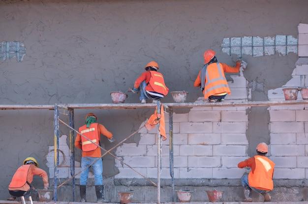 Bouwvakkers pleisterwerk muur en balk met cementpleister mix van cement en zand op de bouwplaats Premium Foto