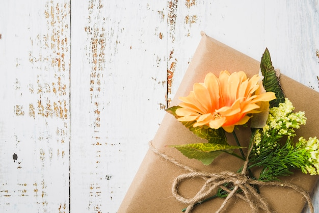 Boven bruin geschenkdoos versierd met bloemen op houten gestructureerde achtergrond Gratis Foto