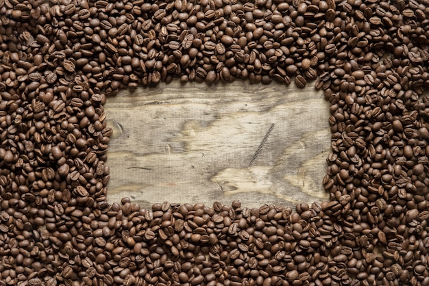 Boven geschoten van een frame van koffiebonen over een houten oppervlakte groot voor achtergrond of het schrijven van tekst Gratis Foto