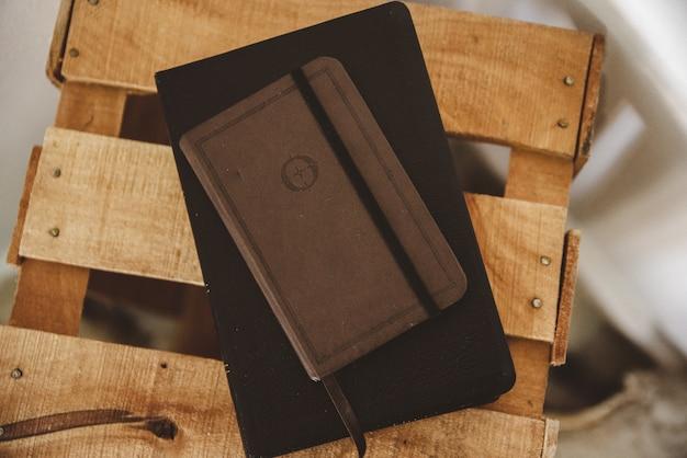 Boven geschoten van een notitieboekje op de bijbel op een houten doos Gratis Foto