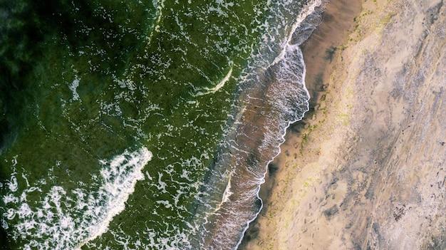 Boven geschoten van strandgolven die naar de kust komen Gratis Foto