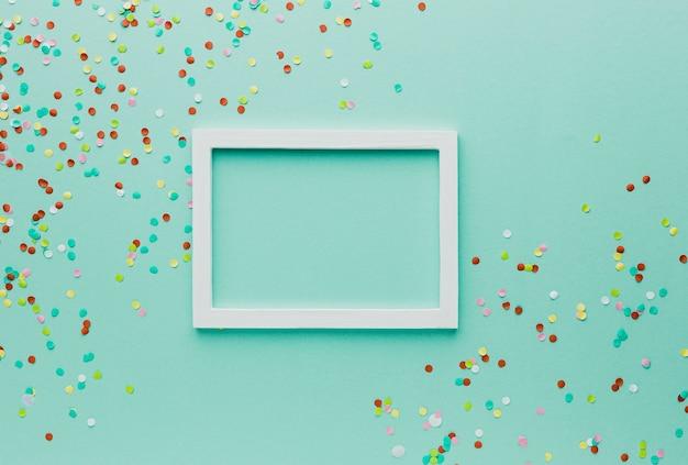 Boven weergave feestdecoratie met frame en groene achtergrond Gratis Foto
