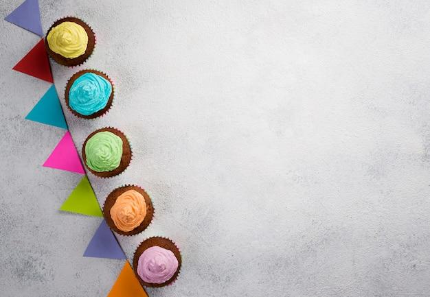 Boven weergave frame met muffins en witte achtergrond Gratis Foto