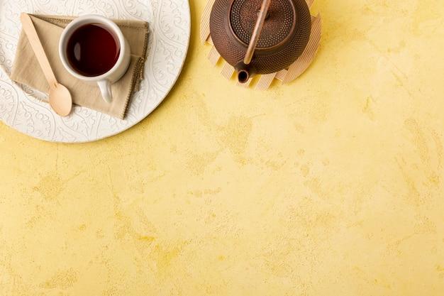 Boven weergave frame met theepot op gele achtergrond Gratis Foto