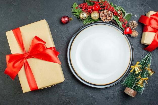 Boven weergave van diner plaat kerstboom fir takken conifer kegel geschenkdoos met rood lint op zwarte achtergrond Gratis Foto