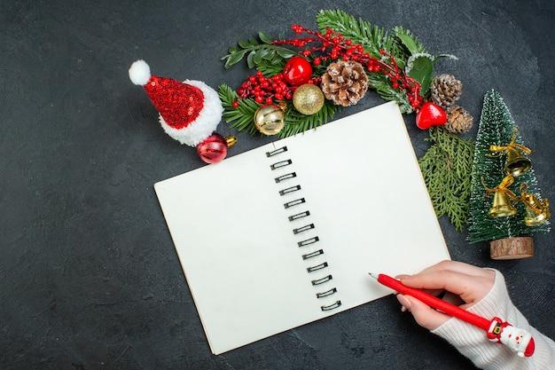 Boven weergave van kerstsfeer met fir takken xsmas boom kerstman hoed hand met een pen op spiraal notebook op donkere achtergrond Gratis Foto