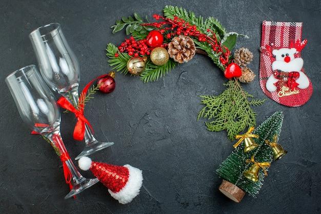 Boven weergave van kerstsfeer met gevallen glazen bekers fir takken xsmas boom sok kerstman hoed op donkere achtergrond Gratis Foto