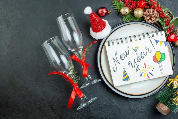 Boven weergave van spiraal notebook met pen op diner plaat kerstboom fir takken conifeer kegel geschenkdoos kerstman hoed gevallen glazen bekers op zwarte achtergrond Gratis Foto