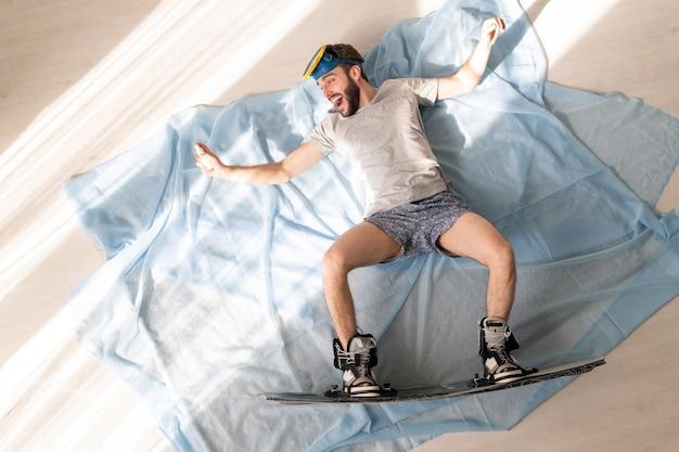 Boven weergave van vrolijke jonge bebaarde man in slipje en t-shirt liggend met uitgestrekte armen op lakens terwijl hij doet alsof hij snowboard thuis isolatie Premium Foto