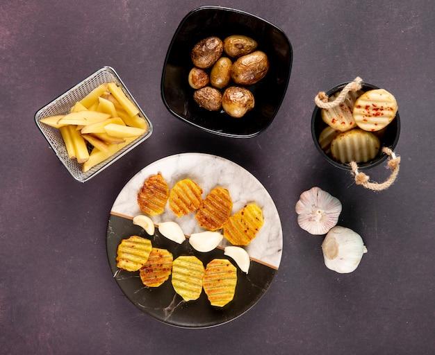Bovenaanzicht aardappelen gegrilde en gehakte aardappelen met gedroogde chili vlokken en knoflook op donkergrijze achtergrond Gratis Foto