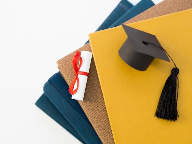 Bovenaanzicht academische cap op boeken Gratis Foto