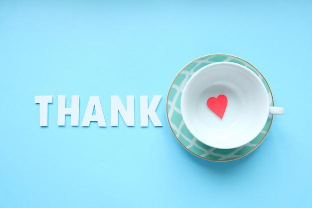 Bovenaanzicht afbeelding beker met zin: dank, volgende en kleine rode hart. Premium Foto