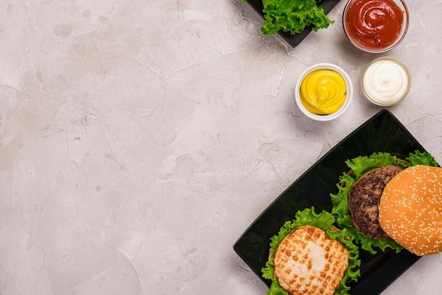 Bovenaanzicht amerikaanse hamburger met verschillende dips Gratis Foto