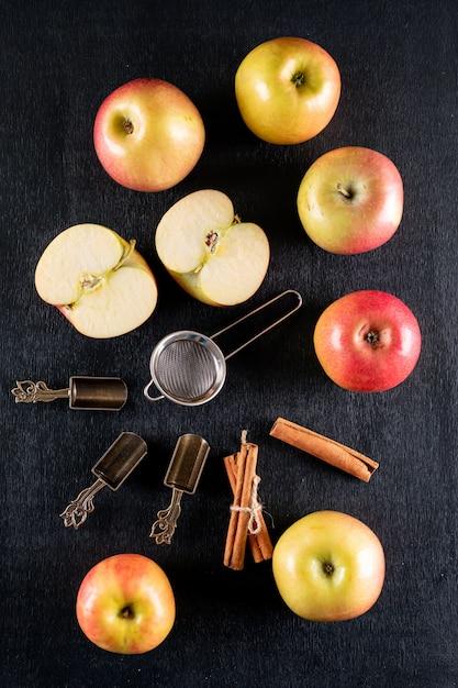 Bovenaanzicht appels met kaneel en thee set op zwarte houten verticaal Gratis Foto