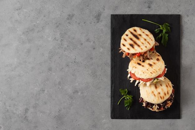 Bovenaanzicht arepas met vlees en tomaten Gratis Foto
