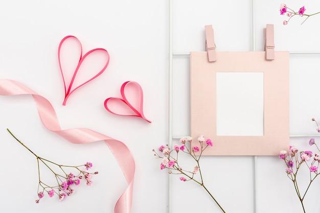 Bovenaanzicht arrangement met frame en hartvormen Gratis Foto