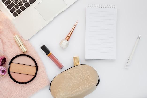 Bovenaanzicht arrangement met make-up artikelen en laptop Gratis Foto