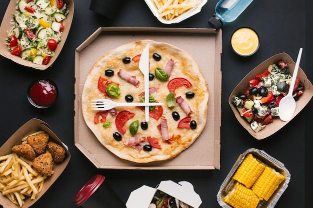Bovenaanzicht arrangement met pizzadoos en salades Gratis Foto