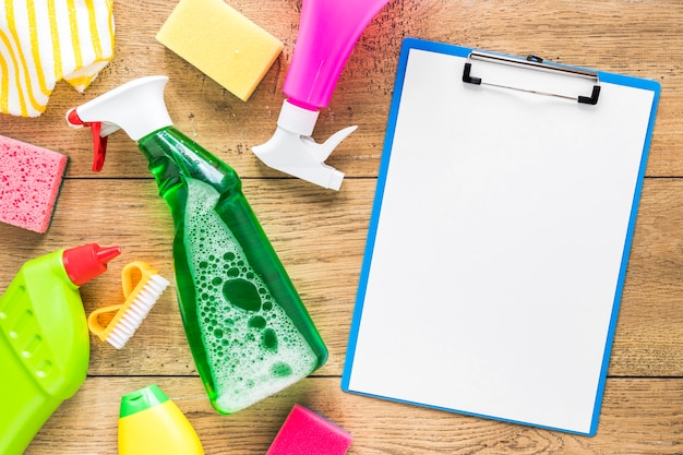 Bovenaanzicht arrangement met reinigingsproducten en klembord Gratis Foto