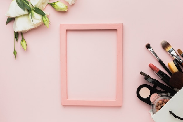 Bovenaanzicht arrangement met roze frame en make-up producten Gratis Foto