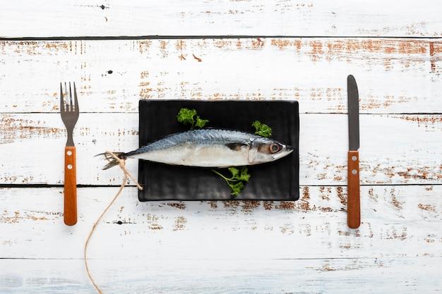 Bovenaanzicht arrangement met vis en servies Gratis Foto