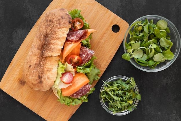 Bovenaanzicht arrangement van heerlijke broodjes op een houten bord Gratis Foto