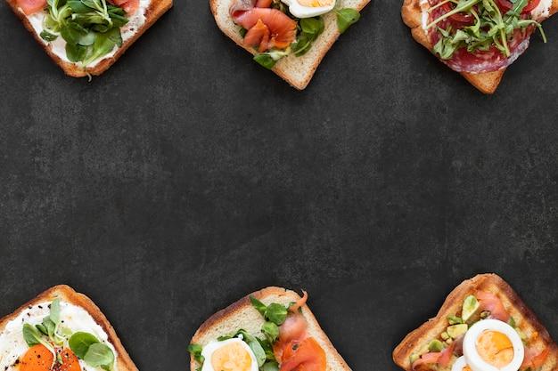 Bovenaanzicht arrangement van heerlijke broodjes op zwarte achtergrond met kopie ruimte Premium Foto